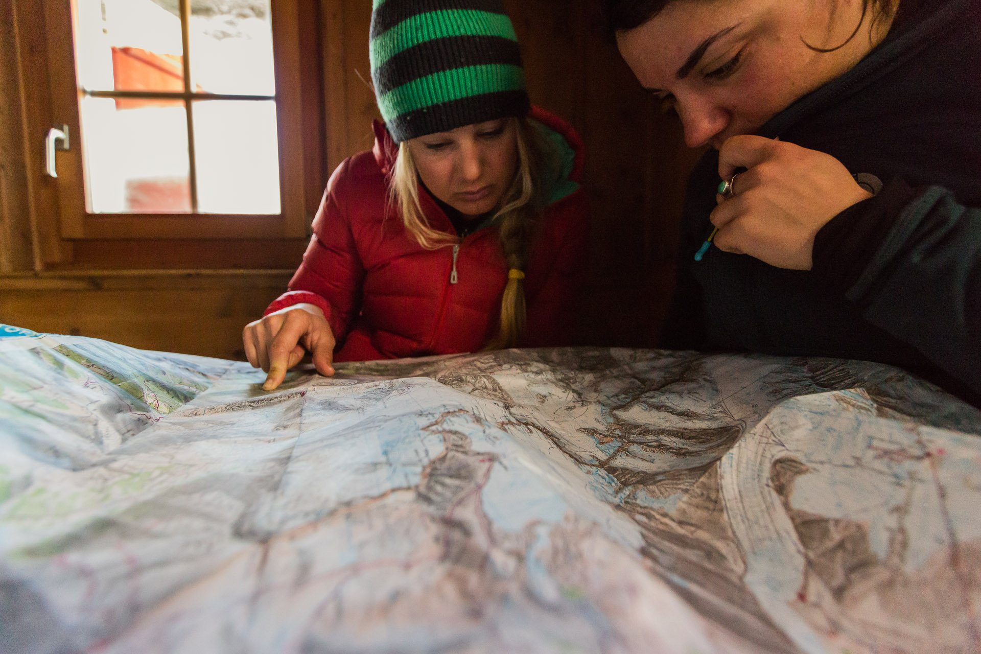 Liz Daley and Maria DeBari check the map before leaving the hut for the day.