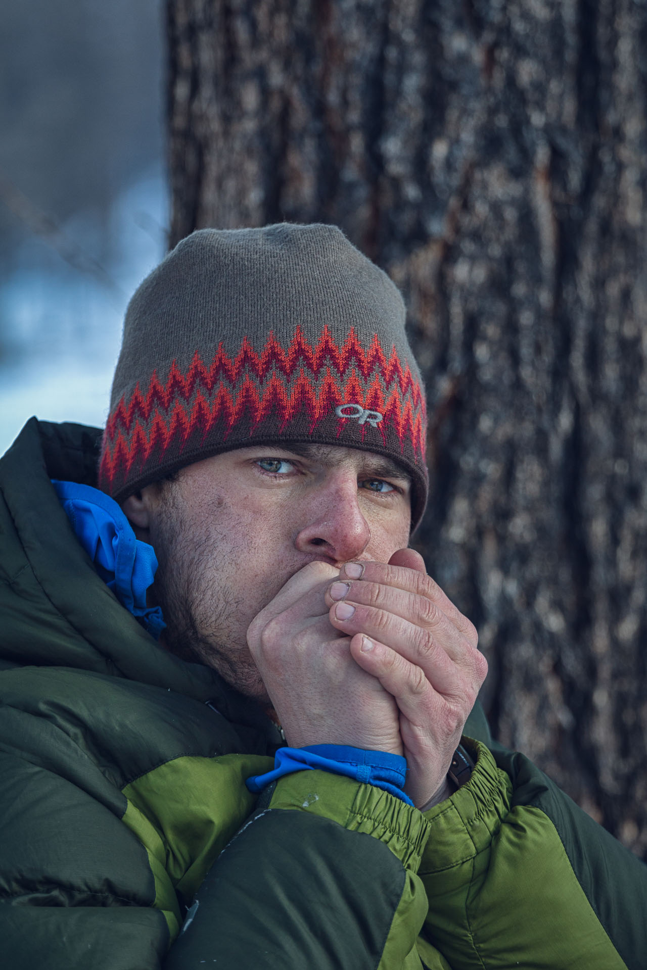 Gregg Treinish pauses from lacing his boots to warm his fingers on a frigid morning.