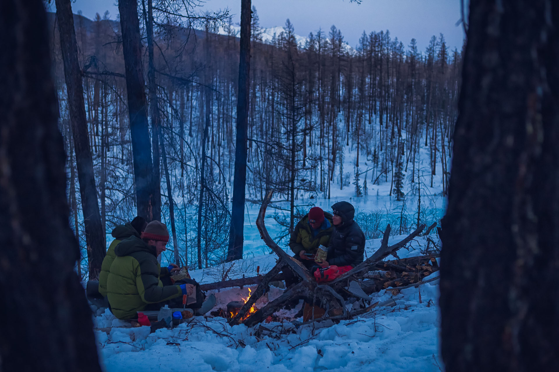 Gregg Treinish, Jason Wilmot, Forrest McCarthy and Rebecca Watters sit by a campfire in a Siberian larch forest above the Utrag River.