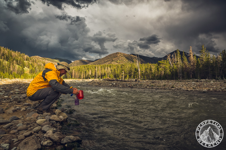 Forrest McCarthy fills a water container in Thorofare Creek